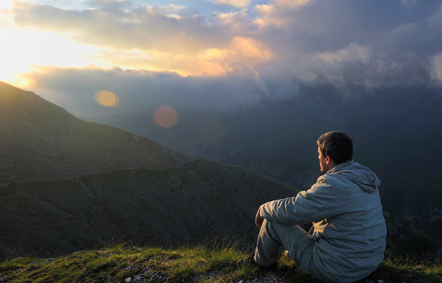 Man sitting on hillside looking at sunrise and vista